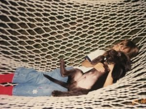 Aged photo of a young girl holding a puppy dog on hammock.