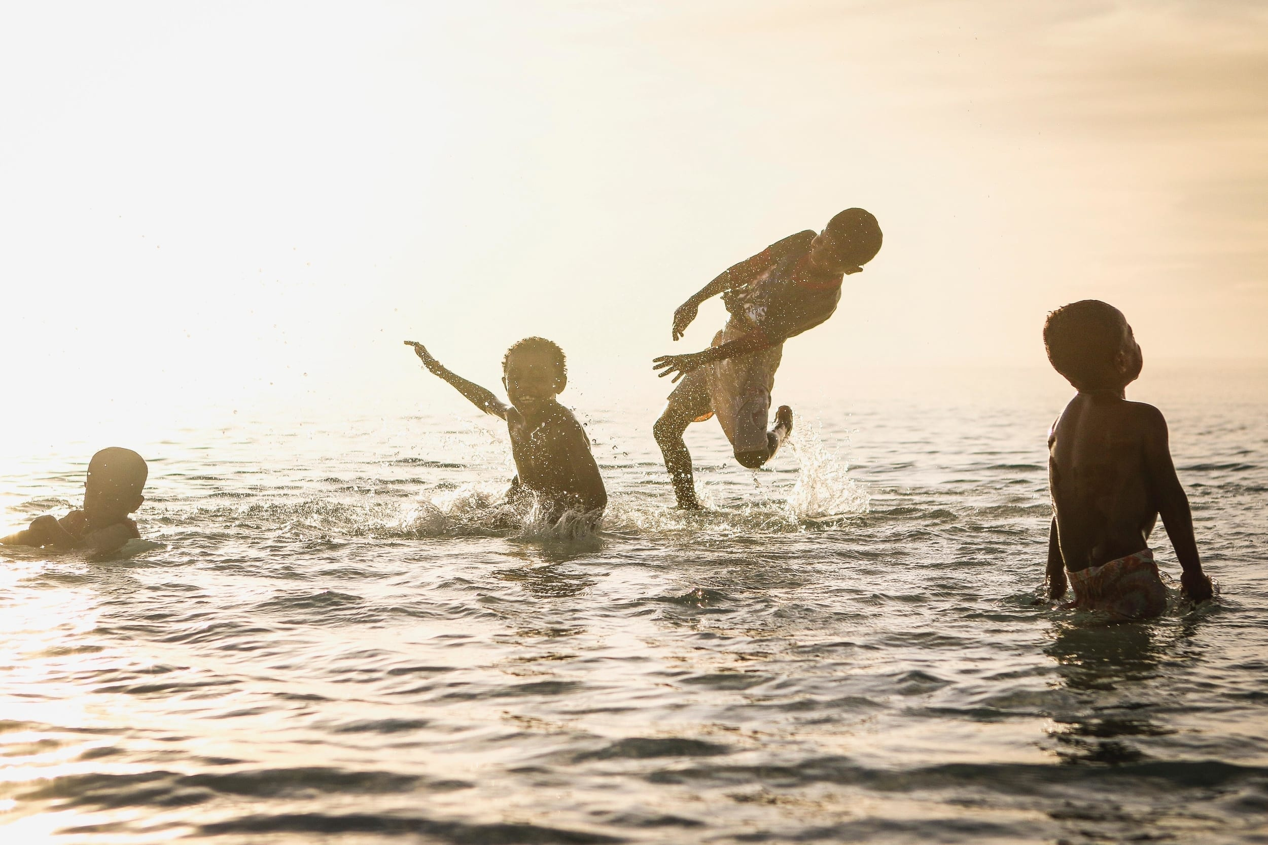 Four boys playing in the water. This photo is from a library of inclusive stock images.